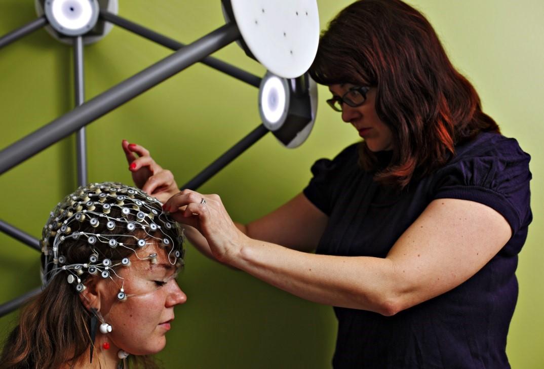 Piia Astikaisen tutkimusryhmässä käytetään EEG- ja MEG-menetelmiä masennukseen liittyvässä aivotutkimuksessa. Kuvassa Piia Astikainen (oikealla) asettaa EEG-mittausverkkoa tutkimusavustajana Astikaisen ryhmässä toimineelle Saara Järveläiselle. Kuva Petteri Kivimäki.